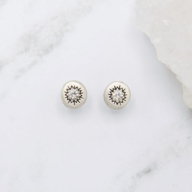 pair of sterling silver sunburst stud earrings with a matte-brushed finish with 3mm crystals