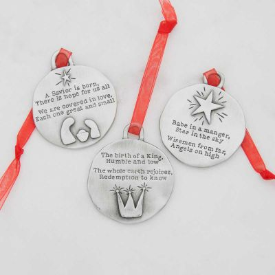 handcrafted babe in a manger pewter ornament set  hung on sheer red ribbon stamped with a Christmas story poem