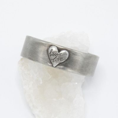 Handcrafted Brave Love emblem cuff with a matte brushed finish
